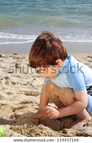 Young boy playing in the sand on the beach