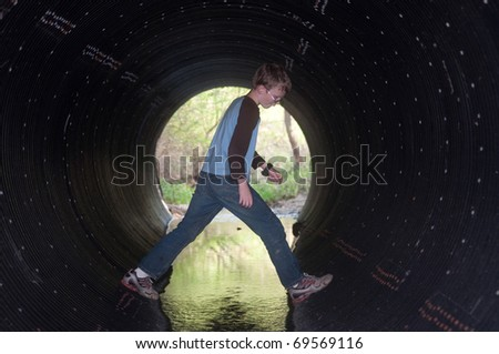 Young boy playing inside of a drainage tunnel