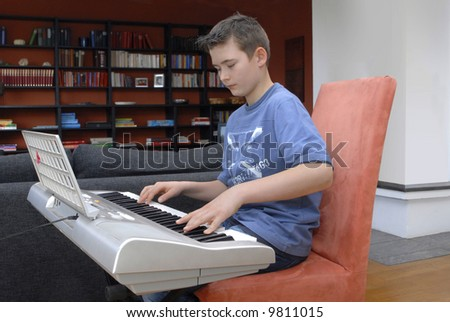 young boy playing keyboard
