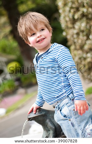 Young boy playing on water fountain
