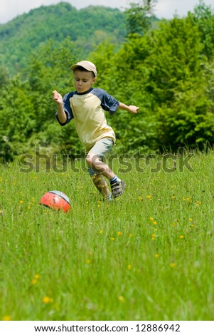 Young boy playing soccer on a meadow with hills in background