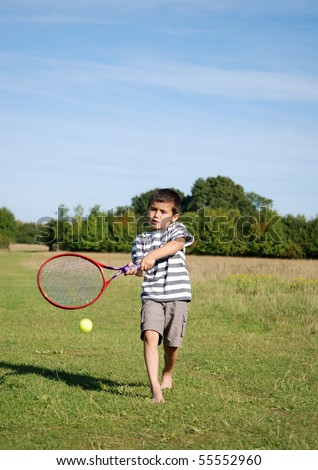 Young boy playing tennis outside