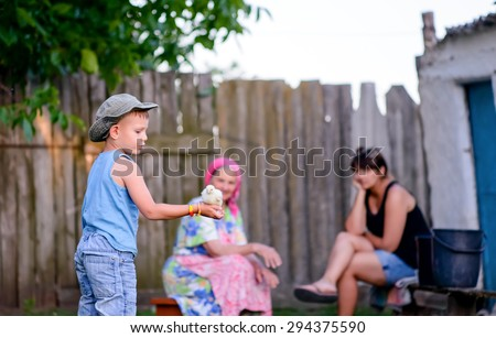 Young boy playing with a baby chicken holding it in the palm of his hand outdoors in the garden watched by his grandmother and mother