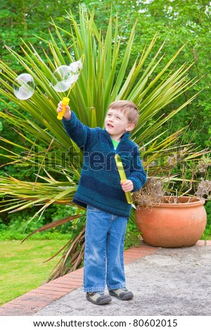 Young boy playing with bubbles outside in a garden