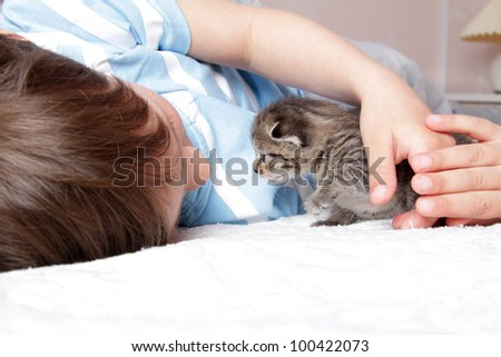 young boy playing with kitten at home