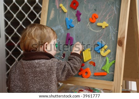 Young boy playing with letters on a blackboard at home