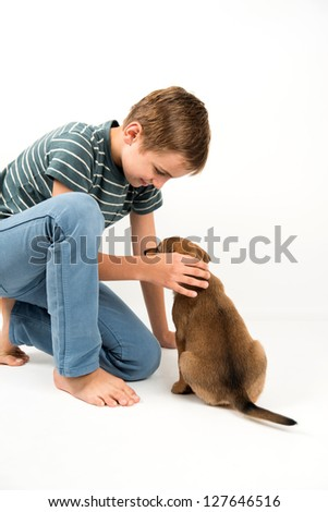 Young Boy Playing with Puppy on White Background