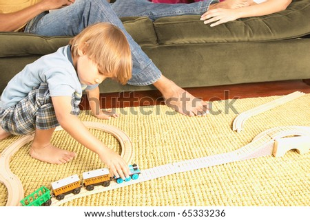 Young boy playing with trains on living room floor
