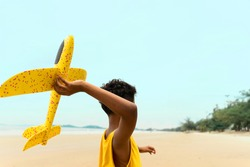 Young boy plays airplane on the beach with happy mood. summer and vacation concept. Half of body composition.
