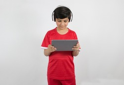 Young boy plays with his tablet isolated on white background