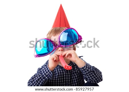Young boy plays with huge pink and blue sunglasses, red paper hat and whistle, birthday party concept, isolated on white