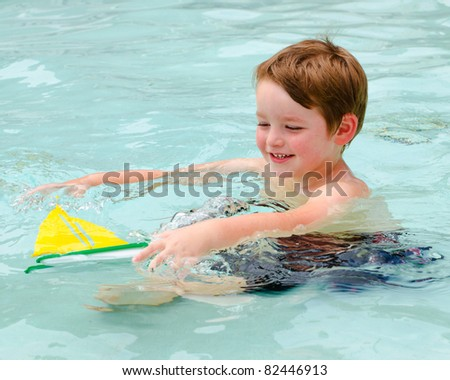 Young boy plays with toy boat while cooling off in pool on hot summer day