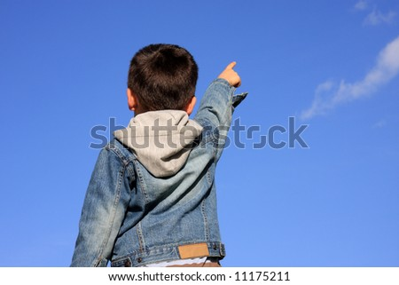 Young boy pointing with his finger to the blue sky