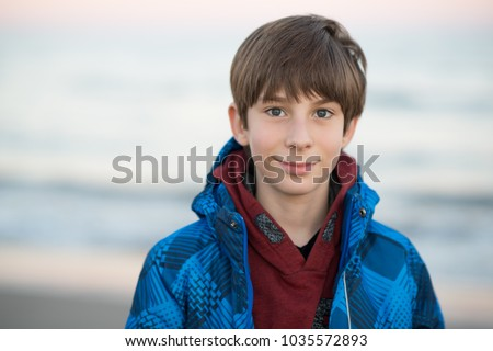 Young boy posing at the winter beach. Cute smiling happy 11 years old boy at seaside, looking at camera. Kid's outdoor portrait. Stock photo ©