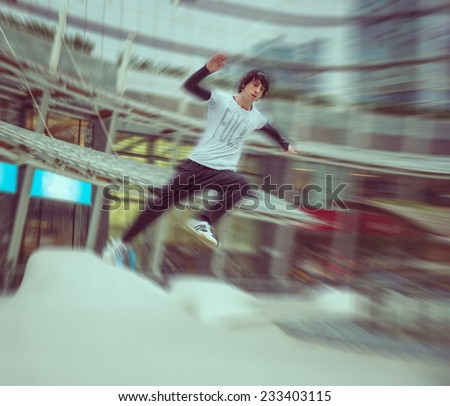 young boy practicing parkour in a urban area. radial blur effect. concept about extreme sports