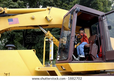 Young boy pretending to drive a giant earth mover