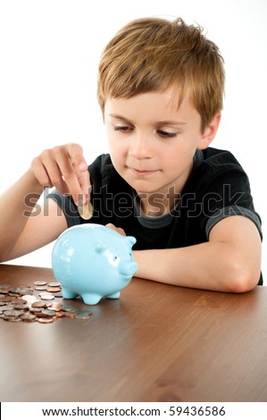 Young Boy Putting Money in Blue Piggy Bank
