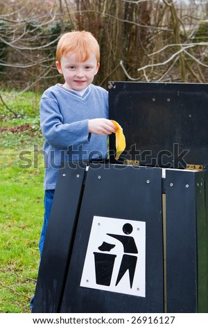 young boy putting waste food scraps into a bin
