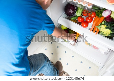 Young Boy Reaching for Snack in Refrigerator Full of Healthy Food Options