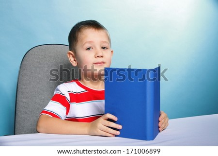 Young boy reading a book, child kid on blue background holding an open book