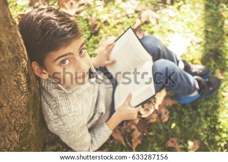 Shutterstock Young boy reading a book outdoors. (Selective focus image toned for vintage effect)