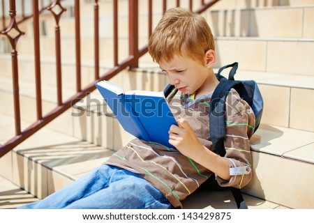 Young boy reading book on school stairs