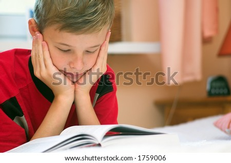 Young boy reading book on the bed