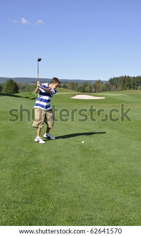 Young boy ready to drive a golf ball on a golf course.