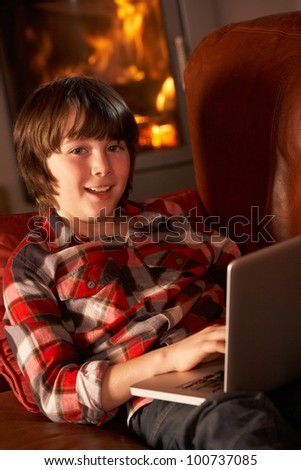 Young Boy Relaxing With Laptop By Cosy Log Fire