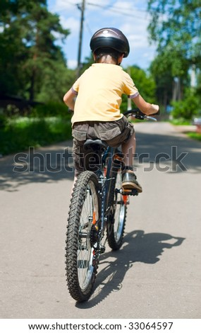 Young boy riding bicycle, shallow dof, focus on rear wheel