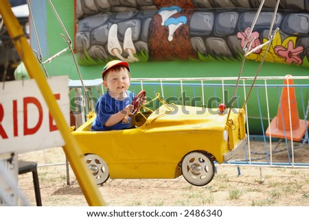 Young boy riding Yellow car at fairground sideshow