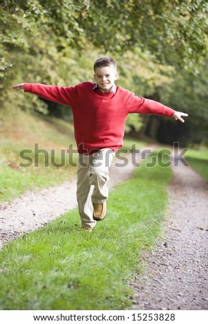 Young boy running along woodland path in autumn