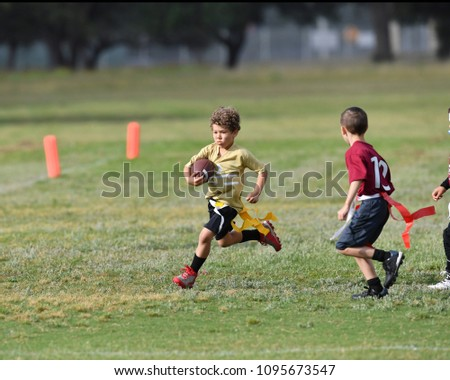 Young boy running with the ball during a youth flag football game