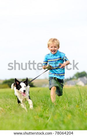 Young boy runs in a green field with his pet collie