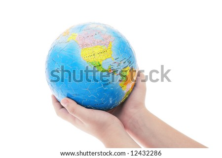 Young boy's hand holding completed globe jigsaw puzzle on white background