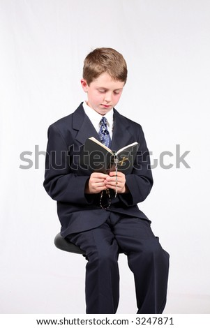 young boy seated reading a bible and holding a rosary