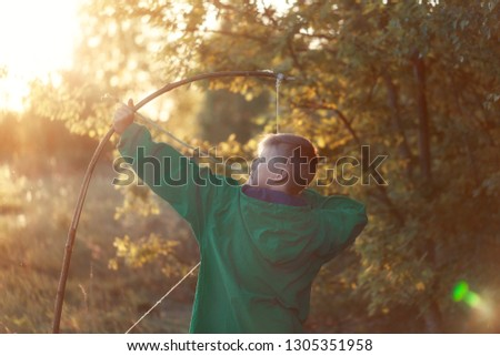 Young boy, shoot with handmade bow and arrow at target on sunset, summertime outdoor. #1305351958