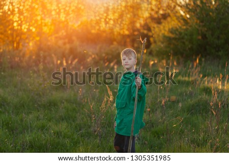 Young boy, shoot with handmade bow and arrow at target on sunset, summertime outdoor. #1305351985