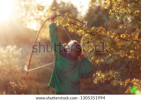 Young boy, shoot with handmade bow and arrow at target on sunset, summertime outdoor. #1305351994