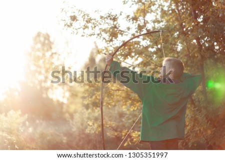 Young boy, shoot with handmade bow and arrow at target on sunset, summertime outdoor. #1305351997