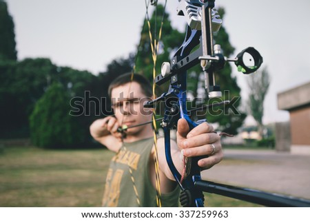 Young boy shooting a bow and arrows