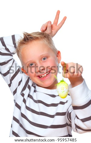 young boy showing easter egg and making rabbit ears behind his head - stock photo