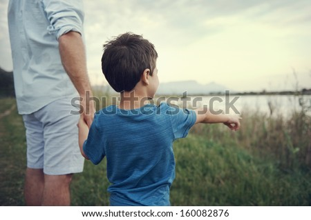 young boy showing his father something while holding hands in the park