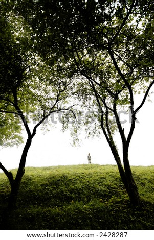 young boy sings on a green hill, wide angle perspective