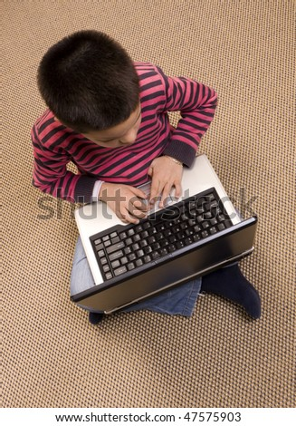 Young boy sit on the floor playing computer games