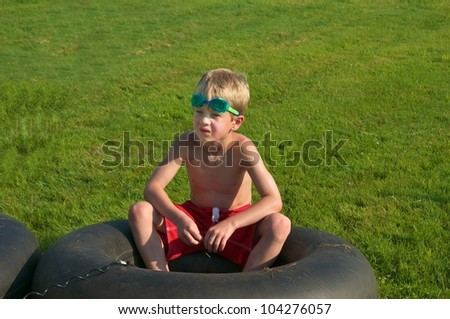 Young boy sits in a tube ready to get in the water
