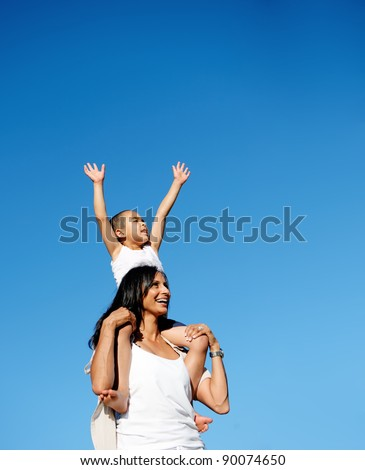 young boy sits on his moms shoulders and reaches for the sky