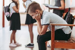 Young boy sitting alone on a bench during break at school