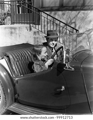 Young boy sitting in the driver's seat of car with his father