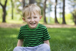 Young boy sitting in the grass at the park laughing